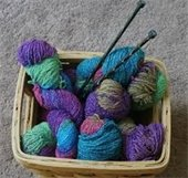 Basket of multicolored yarns with needles stuck in them