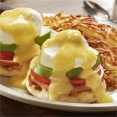 eggs benedict with hash browns in the background