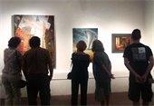 5 people viewing 3 modern paintings