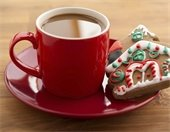 Red coffee cup with gingerbread cookie next to it