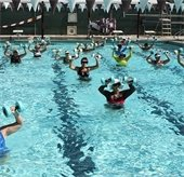 Women in pool with floaty barbells
