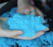 Light blue kinetic sand in a kid's hand