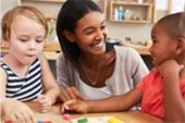 Smiling childcare worker with two kids