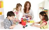 Photo of woman and three children doing crafts