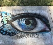 Sidewalk chalk drawing of a blue eye with butterfly wing