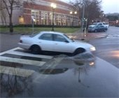 Car going through puddle in front of library