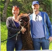 Giving Tree Family Farm owners flanking an alpaca