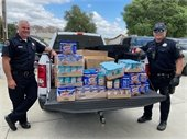 Truck bed full of peanut butter and tuna flanked by two cops