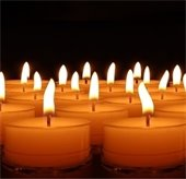 White candles glowing against black background