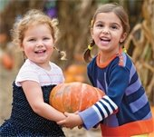 two girls carrying one pumpkin