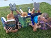 3 kids reading Harry Potter on the grass