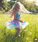 Girl twirling in tall grass
