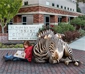 Girl reading with zebra in front of library sign