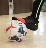 foot on soccer ball in gym