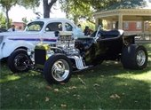 1940's white Ford and a black dragster with giant engine