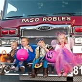 Kids in costume on the bumper of a Paso fire truck