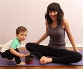 Mom and small son on purple yoga mat
