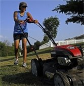 Woman mowing area around her house