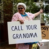 "Lady in grey wig holding sign that says ""call your grandma"""
