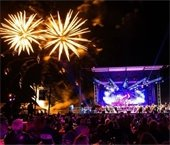 Fireworks exploding over a stage lit with purple lights