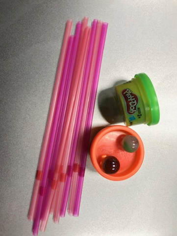 Photo of pink straws, green and orange Play-Doh, two marbles