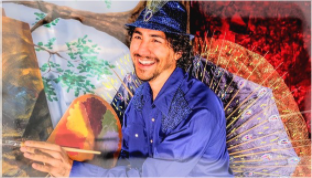 Actor dressed as a colorful peacock stands outside under a tree holding a paintbrush and pallet